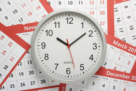 Office clock on a of calendar pages photo