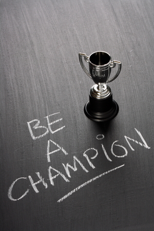 The phrase Be A Champion written by hand on a used blackboard next to a small silver trophy cup  A champion might be a winner or someone who acts as a champion for a cause or process