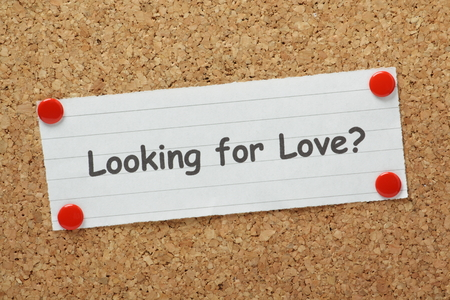 finding love: The phrase Looking For Love  on a paper note pinned to a cork notice board