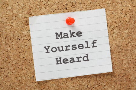 audible: The phrase Make Yourself Heard typed on a piece of lined paper and pinned to a cork notice board