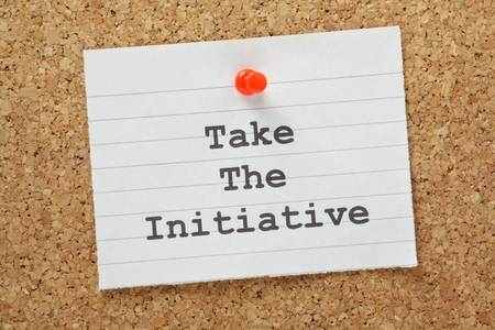 The phrase Take The Initiative typed on a piece of lined paper and pinned to a cork notice board