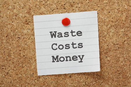 The phrase Waste Costs Money typed on a piece of lined paper and pinned to a cork notice board photo