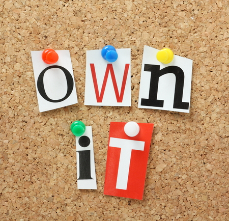 phrase: The phrase Own It in cut out magazine letters pinned to a cork notice board