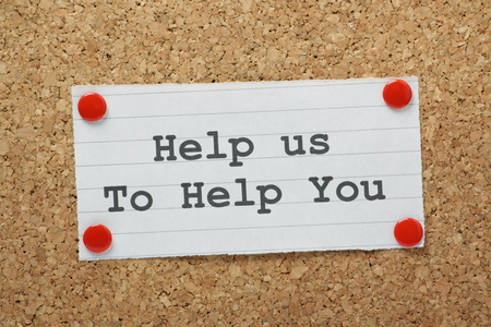 The phrase Help Us To Help You typed on a piece of paper and pinned to a cork notice board