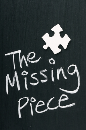 Single blank white jigsaw piece on a blackboard next to text saying The Missing Piece photo