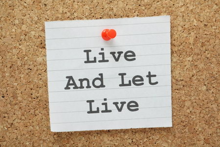 belief system: The phrase Live and Let Live typed on a paper note and pinned to a cork notice board