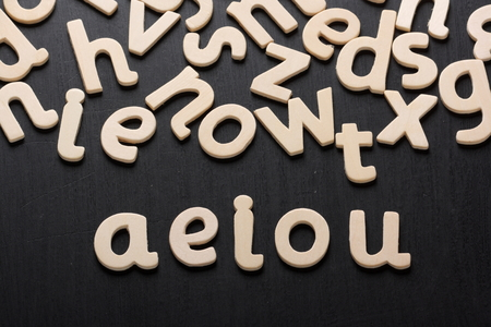 spoken: Wooden letters on a blackboard spell out the vowels used in spoken and written language Stock Photo