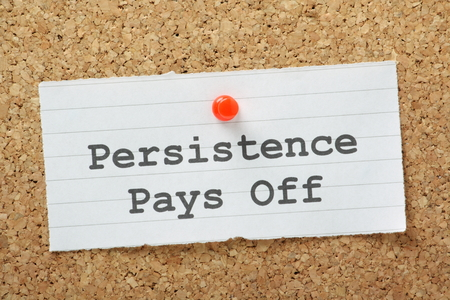 pays: The phrase Persistence Pays Off typed on a paper note and pinned to a cork notice board