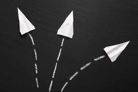 Three paper planes break formation and take flight in different directions across a blackboard surface  photo
