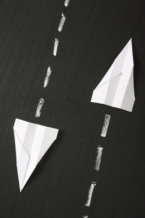 Two paper planes fly in parallel but opposite directions across a blackboard surface photo