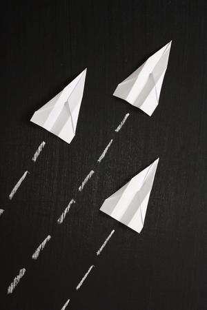 Paper Planes volare in formazione attraverso una superficie lavagna photo