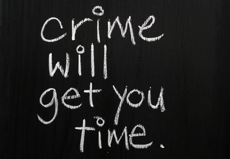 legal advice: The phrase Crime Will Get You Time written in white chalk on a used blackboard