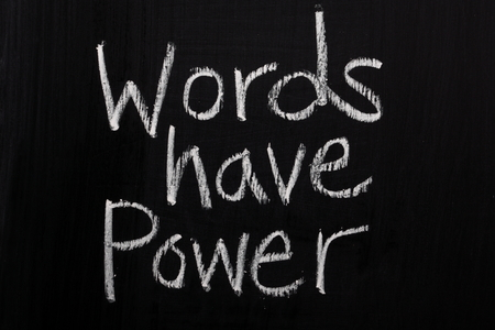 phrase: The phrase Words Have Power written in white chalk on a used blackboard