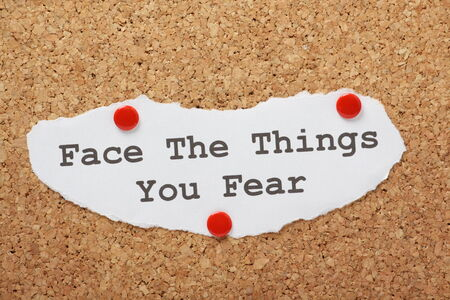 The phrase Face The Things You Fear on a piece of paper pinned to a cork notice board