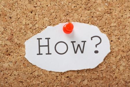 Het woord Hoe getypt op een stuk papier en vastgemaakt aan een kurk prikbord