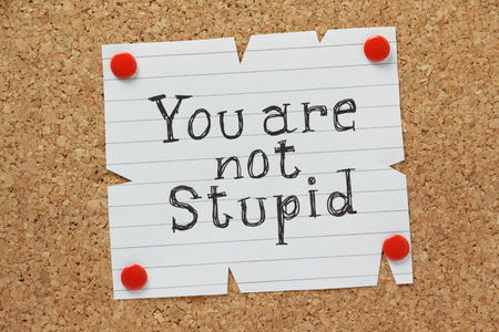 The phrase You Are Not Stupid written by hand on a piece of paper pinned to a cork notice board photo