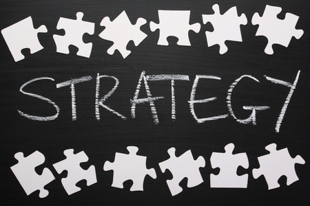 The word Strategy written on a blackboard with a border of blank white pieces of a jigsaw puzzle photo