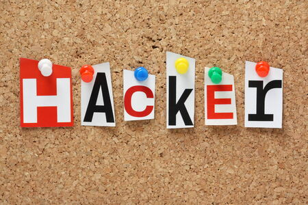 law breaker: The word Hacker in cut out magazine letters pinned to a cork notice board Stock Photo