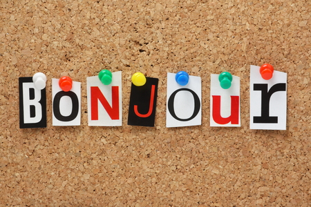 The French word Bonjour in cut out magazine letters pinned to a cork notice board Banque d'images