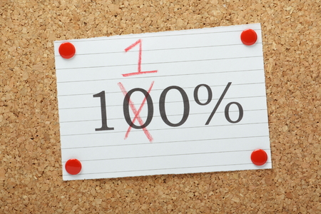 exceeding: One hundred percent changed to one hundred and ten percent on a paper reminder pinned to a cork notice board Stock Photo