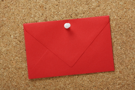 closed corks: A sealed red envelope pinned to a cork notice board