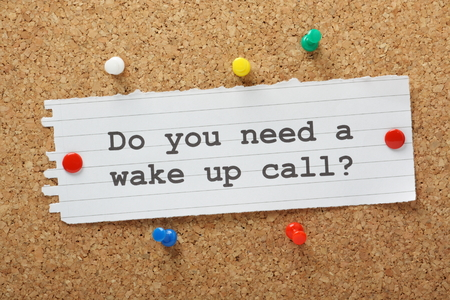 The question Do You Need a Wake Up Call  typed on a paper reminder note and pinned to a cork notice board