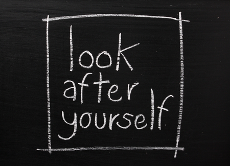 look after:  Look After Yourself written on a used blackboard