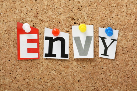 seven deadly sins: The word Envy, one of the seven deadly sins in cut out magazine letters pinned to a cork notice board Stock Photo