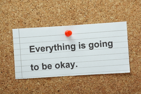 The phrase Everything is going to be Okay typed on a piece of paper and pinned to a cork notice board
