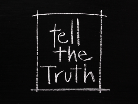phrase: The phrase Tell The Truth written by hand in white chalk on a blackboard surface