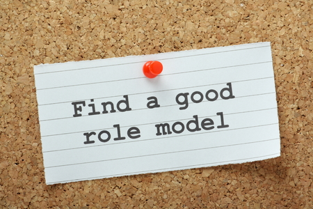 The phrase Find A Good Role Model typed on a piece of paper and pinned to a cork notice board
