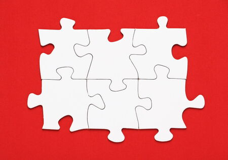 conundrum: Blank white jigsaw puzzle pieces on a red background