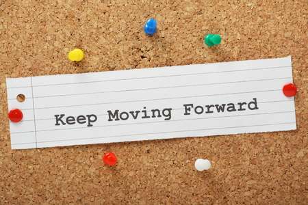 The phrase Keep Moving Forward on a cork notice board Standard-Bild