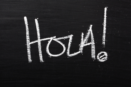 The Spanish word Hola written in white chalk on a blackboard  The word is used as an informal greeting that means hello or hi photo