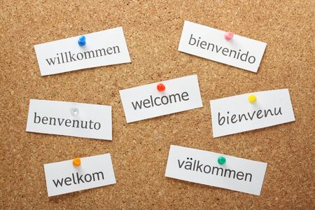 willkommen: The word Welcome translated into the principal languages of western and northern Europe pinned on a cork notice board Stock Photo