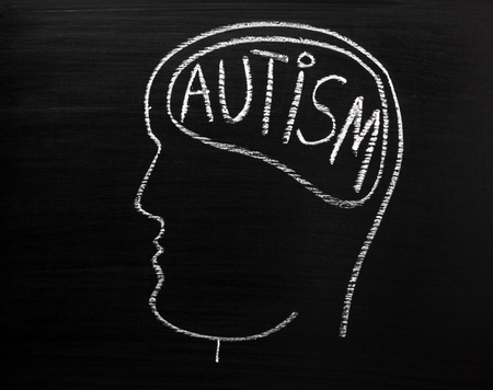 autistic: Human head in profile on a blackboard with the word Autism written in the brain area Stock Photo