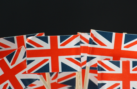 britain flag: Miniature Union Jack Flags in front of a black background with copy space Stock Photo