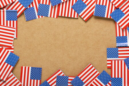 Miniature flags of the United States of America arranged to form a border on a cardboard background with copy space
