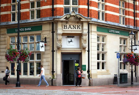 financial services: Reading, England - August 28th, 2014: A woman exits the Reading branch of Lloyds Bank as other people pass by. The UK Treasury owns 25% of Lloyds after a 20bn bailout during the 2008 financial crisis