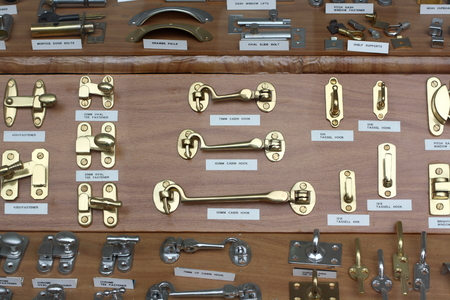 ironmongery: Londres, Inglaterra - 04 de septiembre 2014: Una pantalla escaparate de ganchos de cabina de metal, tornillos, pernos y cierres para la venta en una tienda de hardware Editorial