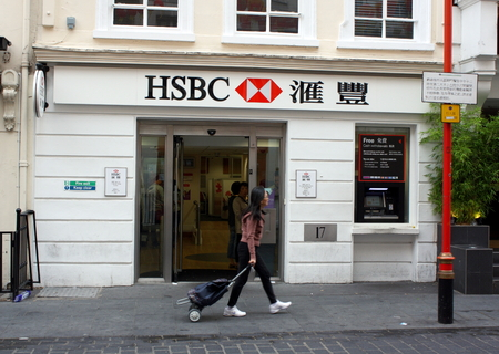 bank branch: London, England - Sept 4th, 2014: A pedestrian passes by the front entrance of the Gerrard Street branch of HSBC Bank in London\\ Editorial