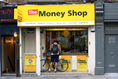 payday: London, England - Sept 4th, 2014: A man stands at the window of The Money Shop in the Soho area of London. The Money Shop provides payday loans, pawn brokering and other financial services in the UK
