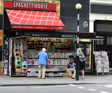 London, England - Sept 4th, 2014: A woman stands at a newspaper kiosk in front of the vendor as another woman passes by on the street in central London, England on September 4th, 2014