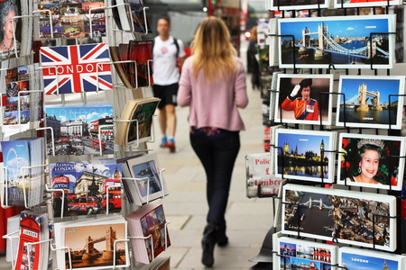 viewpoints: London, England - Sept 11th, 2014: Pedestrians moving along a busy street in London as viewed between two display stands of postcards depicting scenes of London and the British Royal Family Editorial