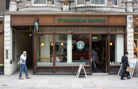 shop window: London, England - Sept 11th, 2014: People passing by and entering a Starbucks store in Central London, England. Starbucks has outlets in more than 50 countries worldwide.