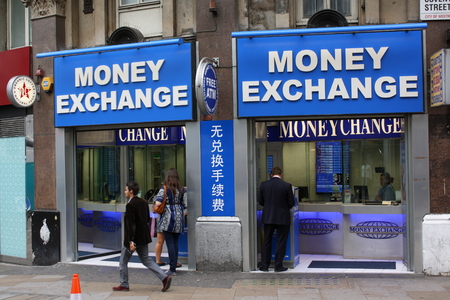 overseas: London, England - Sept 4th, 2014: A man passes by a Money Exchange where other people are using the ATM machines. The outlets are owned by ChangeGroup which opened their first branch in London in 1992