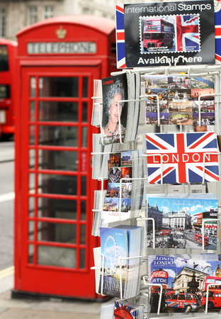 mementos: London, England - Sept 11, 2014: A display stand of postcards in a central London Street with scenes of London and the British Queen. In the background is a red telephone box and part of a red bus. Editorial