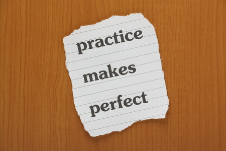 The phrase Practice Makes Perfect typed on a piece of lined paper and laid on a false wooden background or desktop photo