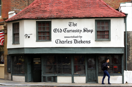 however: London, England - Sept 11, 2014: A pedestrian passes by The Old Curiosity Shop in London, a 16th century building generally used for retail purposes. However, any connection with Charles Dickens is unproven. Editorial