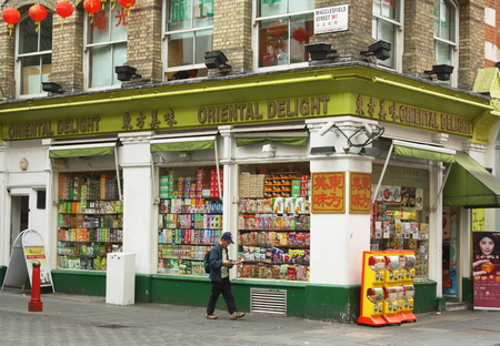 provisions: London, England - Sept 4th, 2014: A man walks by the Oriental Delight supermarket in Macclesfield Street in Londons Chinatown District - a community of restaurants and businesses since the 1950s